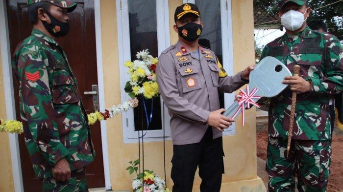 Waka Polres Subang, Kompol Dony Eko Wicaksono (tengah) menyerahkan kunci rumah kepada Danramil Purwadadi, Subang disaksikan Kopka Hamim (kiri) di Dusun Kaliwadas, Desa Pagon, Kecamatan Purwadadi, Subang, Kamis (21/1/2021)