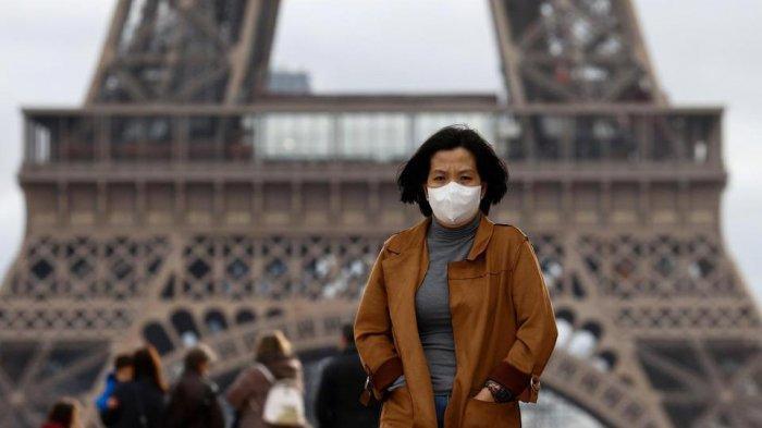Ilustrasi, seorang perempuan memakai masker pelindung saat penularan virus korona di lapangan terbuka Trocadero di depan Menara Eiffel di Paris, Prancis.