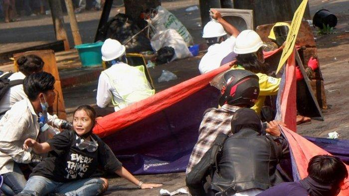 Protesters lie on the ground after police opened fire to disperse an anti-coup protest in Mandalay, Myanmar, (3/3/2021). Among them Angel, 19, bottom left, also known as Kyai Sin, took cover before she was shot in the head.