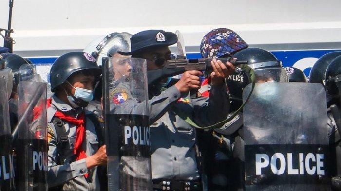 Seorang polisi (tengah) mengacungkan senapannya dalam bentrokan melawan massa yang ikut dalam demonstrasi menentang kudeta militer Myanmar di Naypyidaw, pada 9 Februari 2021.