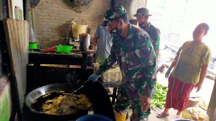 Satu di antara Personel Satgas TMMD ke-109 Kodim 0201/ BS Medan sedang membantu menggoreng pisang bersama orang tua asuh, di Kelurahan Tanah Enam Ratus, Kecamatan Medan Marelan, Kota Medan, Senin (5/10/2020).
