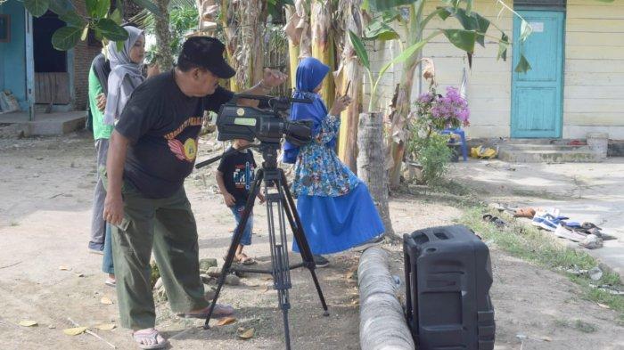 Pengasuh Sanggar Seni Pusaka Aru Teater Garis Lurus Langkat, Datok Seri Drs. H. Zainal Arifin.AKAi. Si, M.Pd sedang mengngambil gambar Tari Ber Ahoii mengirik padi di desa securei, Langkat, Sumatera Uatara.