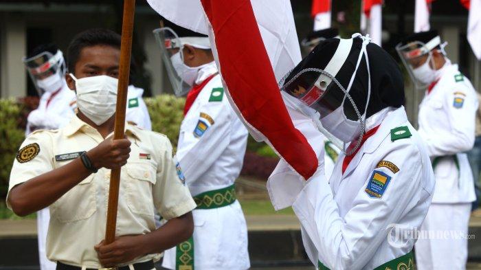 Pasukan Pengibar Bendera Pusaka (Paskibraka) Kota Bandung Tahun 2020 mengenakan masker dan pelindung wajah menjalani prosesi pengukuhan di Balai Kota Bandung, Jalan Wastukencana, Kota Bandung, Jumat (14/8/2020). Pada acara tersebut, Wakil Wali Kota Bandung, Yana Mulyana mengukuhkan sebanyak 10 orang anggota Paskibraka yang akan menjadi petugas upacara Peringatan HUT ke-75 Kemerdekaan Republik Indonesia, 17 Agustus 2020 di Balai Kota Bandung. Jumlah anggota Paskibraka yang bertugas tahun ini tidak sebanyak tahun-tahun sebelumnya karena pertimbangan keselamatan di saat pandemi Covid-19. (TRIBUN JABAR/GANI KURNIAWAN)