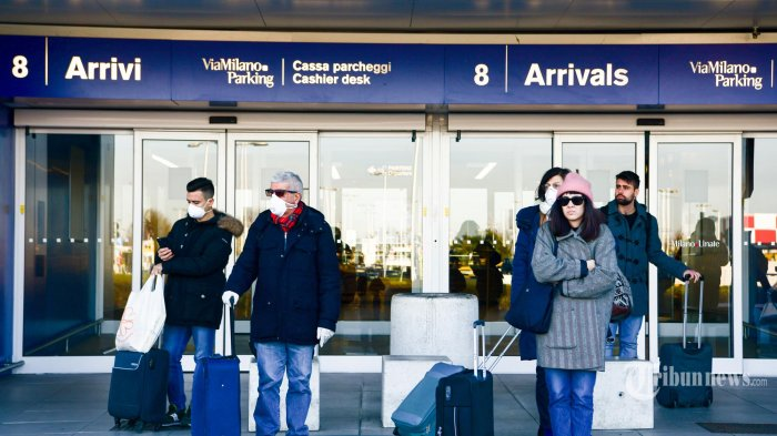 Penumpang yang mengenakan masker wajah, di tengah kekhawatiran tentang wabah COVID-19, menunggu di luar terminal kedatangan di Bandara Linate di Milan. Italia. Minggu (8/3/2020). Pemerintah Italia mengambil langkah drastis dalam upaya untuk menghentikan penyebaran coronavirus mematikan yang melanda dunia, dengan mengkarantina paksa 15 juta orang di wilayah luas Italia utara hingga 3 April, kerena lebih dari 230 kematian, Italia telah mencatat kematian terbanyak akibat penyakit COVID-19 di negara mana pun di luar China, tempat wabah dimulai pada bulan Desember.(AFP/Piero CRUCIATTI) *** Local Caption *** Pemerintah Indonesia melalui Kementerian Luar Negeri (Kemenlu) mengeluarkan larangan pendatang dari sejumlah negara untuk masuk wilayah Indonesia.   Pendatang yang dilarang adalah mereka yang datang atau punya riwayat perjalanan dari wilayah-wilayah tertentu dari 4 negara yaitu China, Iran, Korea Selatan, dan Italia.