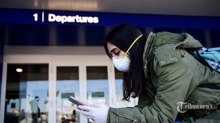 Seorang penumpang yang mengenakan masker pelindung, di tengah kekhawatiran tentang wabah COVID-19, melihat teleponnya di Bandara Linate di Milan, Italia. Minggu (8/3/2020). Pemerintah Italia mengambil langkah drastis dalam upaya untuk menghentikan penyebaran coronavirus mematikan yang melanda dunia, dengan mengkarantina paksa 15 juta orang di wilayah luas Italia utara hingga 3 April, kerena lebih dari 230 kematian, Italia telah mencatat kematian terbanyak akibat penyakit COVID-19 di negara mana pun di luar China, tempat wabah dimulai pada bulan Desember.  (AFP/Piero CRUCIATTI) *** Local Caption *** Pemerintah Indonesia melalui Kementerian Luar Negeri (Kemenlu) mengeluarkan larangan pendatang dari sejumlah negara untuk masuk wilayah Indonesia.   Pendatang yang dilarang adalah mereka yang datang atau punya riwayat perjalanan dari wilayah-wilayah tertentu dari 4 negara yaitu China, Iran, Korea Selatan, dan Italia.