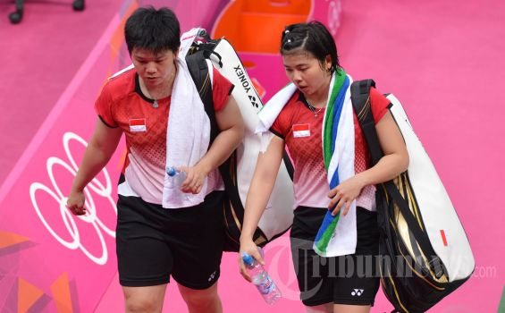 Indonesia's Greysia Polii (R) and Meilana Jauhari (L) leave the court after their women's doubles badminton match against South Korea's Kim Min Jung and Ha Jung Eun at the London 2012 Olympic Games in London on July 31, 2012. The South Korean pair won the match 18-21, 21-14, 21-12. Eight women badminton players at the Olympics were charged by the sport's governing body on August 1, 2012, with 'throwing' matches to secure an easier draw in the next round. Four pairs in the women's doubles competition - one from China, one from Indonesia and two from South Korea - could be disciplined after the Badminton World Federation (BWF) took action. AFP PHOTO / ADEK BERRY