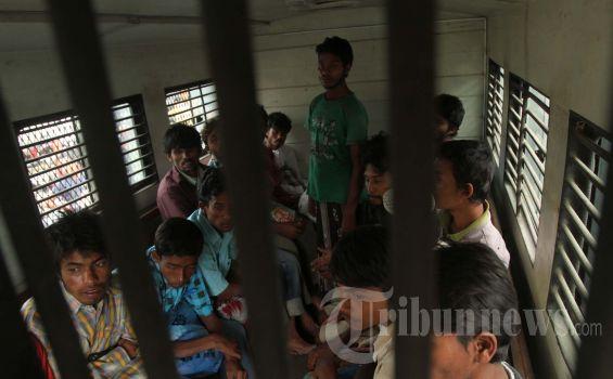 Warga rohingya dievakuasi menggunakan mobil tahanan polisi ke tempat penampungan sementara di bekas kantor imigrasi Peunteut, Kecamatan Blang Mangat, Lhokseumawe, Rabu (27/2/2013). 121 warga rohingnya itu yang tedampar di lepas pantai kawasan desa Cot Trueng, Kecamatan Muara Batu, Aceh Utara telah mendapat bantuan dari warga setempat. (Serambi INDONESIA/ZAKI MUBARAK)