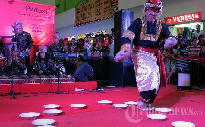 Tom Ibnur, maestro tari asal Minang menampilkan tari piring dalam acara jelang pementasan teater Legendra Padusi, di Blok B Pasar Tanah Abang, Jakarta, Selasa (6/5/2013). Pementasan Legendra Padusi yang disutradarai oleh Rama Soeprapto dan Nia Dinata tersebut akan dipentaskan di Taman Ismail Marzuki, pada 11-12 Mei mendatang. TRIBUNNEWS/DANY PERMANA