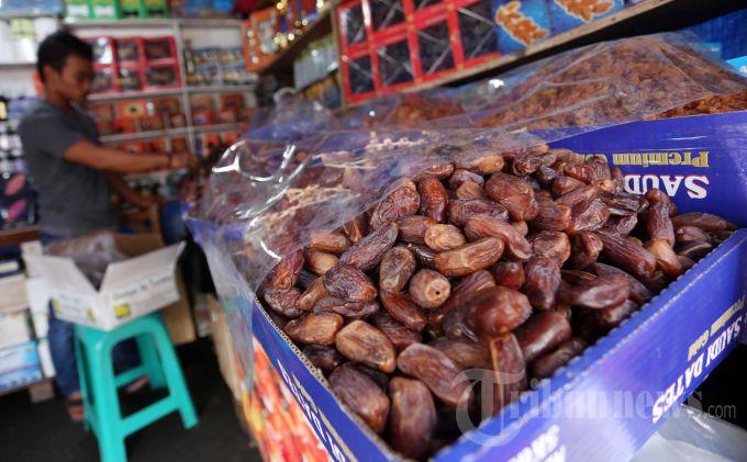 Pedagang buah kurma melayani pembeli di Kawasan Tanahabang, Jakarta Pusat, Rabu (10/7/2013). Buah kurma untuk takjil ini harganya bervariasi, mulai dari Rp 25.000 per kilo gram hingga Rp 300.000 per kilogram. Pada hari pertama puasa, Ia mengaku belum ada peningkatan penjualan. (Warta Kota/Angga Bhagya Nugraha)