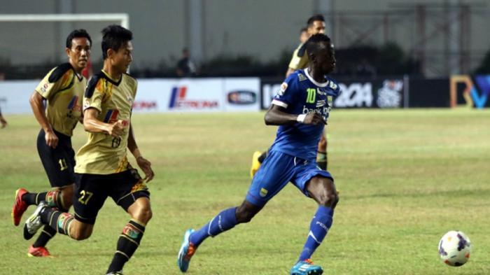 Pemain Persib Bandung, Makan Konate (biru) menggiring bola dibayangi pemain Mitra, Dedi Gusmawan.