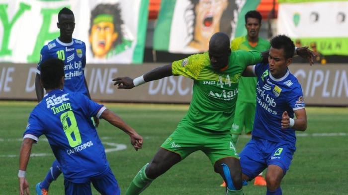 Bek Persebaya, John Onorionde Khughegbe (hijau) mengamankan bola dari serbuan pemain Persib, Agung Pribadi.