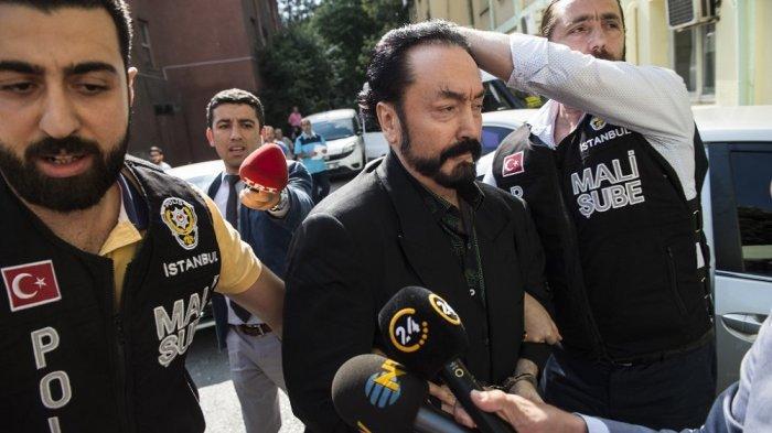 Foto ini diambil pada 11 Juli 2018 saat petugas polisi Turki mengawal Adnan Oktar atau Harun Yahya (tengah) di Istanbul. Saat itu, ia ditangkap atas tuduhan penipuan.