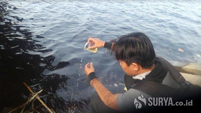 Kondisi air Bengawan Solo di Lamongan yang berubah warna menjadi hitam, diduga tercemar limbah, Selasa (10/12/2019). SURYA.co.id/Hanif Manshuri