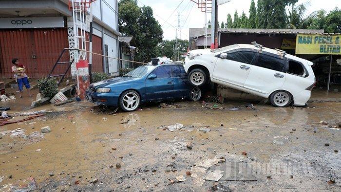 Seorang warga menyaksikan puluhan kendaraan hancur pasca banjir yang merendam kawasan Pondok Gede Permai, Jatiasih, Bekasi, Jawa Barat, Kamis (2/1/2020). Sebelumnya diketahui bahwa kawasan tersebut diterjang banjir dengan ketinggian air mencapai lima meter yang membuat ratusan rumah warga nyaris tenggelam dan yang terlihat hanya bagian atap.