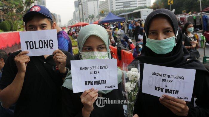 Penggiat Anti Korupsi membawa poster saat melakukan aksi pada Hari Bebas Kendaraan Bermotor di kawasan Bundaran HI Jakarta, Minggu (8/9/2019). Aksi tersebut untuk menolak revisi UU KPK yang dianggap melemahkan kewenangan lembaga anti rasuah itu. TRIBUNNEWS/IRWAN RISMAWAN