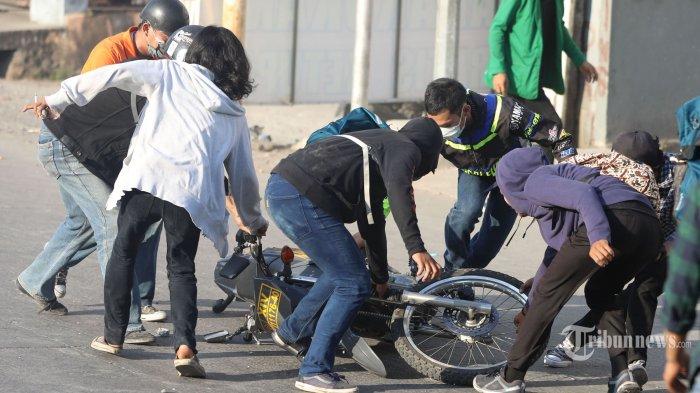 Sejumlah mahasiswa menyeret motor Polisi saat mengikuti aksi unjuk rasa di Jalan AP Pettarani, Makassar, Sulawesi Selatan, Selasa (24/9/2019). Aksi unjuk rasa mahasiswa gabungan dari universitas se-Makassar yang menuntut penolakan terhadap pengesahan UU KPK dan RKUHP itu berujung bentrok saat dibubarkan paksa oleh aparat kepolisian. Tribun Timur/Sanovra Jr