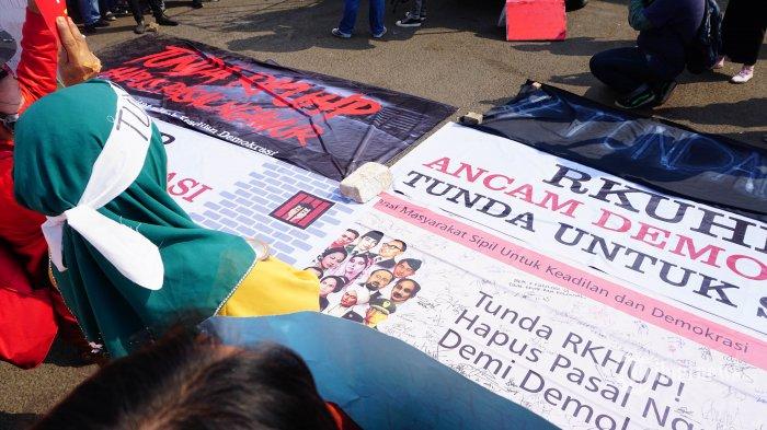 Massa menggelar aksi menolak pengesahan Rancangan Kitab Undang-undang Hukum Pidana (RKUHP) di depan Kompleks Parlemen, Senayan, Jakarta Pusat, Senin (16/9/2019). Aksi yang diwakili oleh buruh, mahasiswa, dan rakyat sipil ini menolak DPR mengesahkan RKUHP yang dianggap dapat mengancam rakyat Indonesia. Tribunnews/Muhammad Iqbal Firdaus