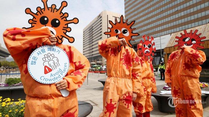 Anggota Pusat Lingkungan dan Kesehatan Warga Asia mengenakan masker yang menggambarkan coronavirus tampil selama kampanye tindakan dalam pencegahan terhadap coronavirus COVID-19, di Seoul pada Kamis (26 Maret 2020). Presiden AS Donald Trump telah meminta alat uji virus coronavirus baru dari Korea Selatan, Moon Jae-in mengatakan pada 25 Maret, ketika Washington mendorong untuk segera membuka kembali ekonomi terbesar di dunia itu. (AFP/YONHAP)