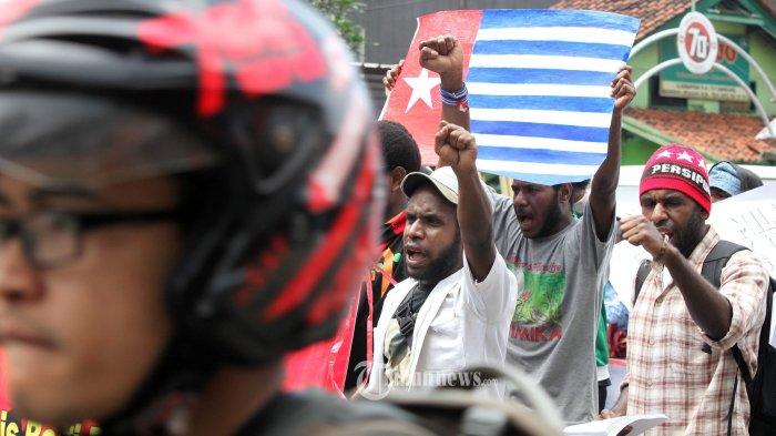 Mahasiswa yang tergabung dalam Aliansi Mahasiswa Papua (AMP) Komite Kota Bandung membentangkan bendera bintang kejora saat melakukan unjuk rasa memperingati 54 Tahun Hari Aneksasi Papua berjalan melintasi Jalan Karapitan, Kota Bandung, Senin (2/5/2016). Mereka menuntut menarik pasukan organik (TNI dan Polri) dan non organik dari seluruh tanah Papua. hentikan eksploitasi dan tutup seluruh perusahaan milik kaum imperialis, dan berikan kebebasan dan hak menentukan nasib sendiri bagi rakya Papua sebagai solusi demokrasi. TRIBUN JABAR/GANI KURNIAWAN
