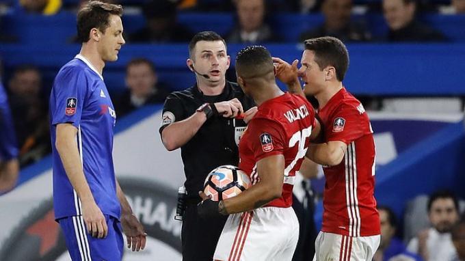 Dua pemain Manchester United, Ander Herrera (paling kanan) dan Antonio Valencia mendatangi wasit Michael Oliver.