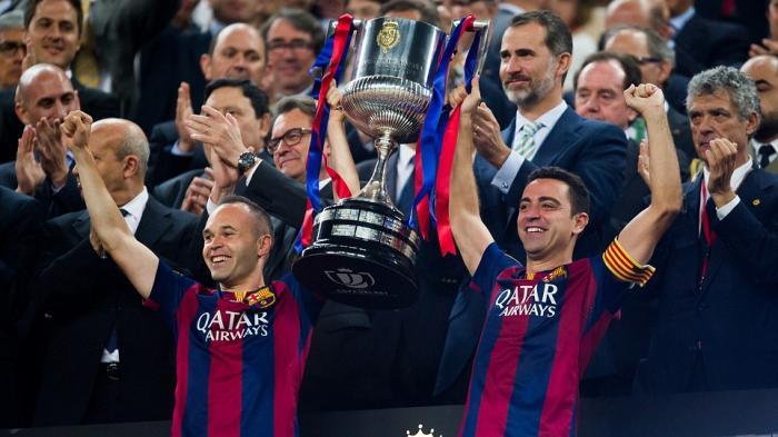 Andres Iniesta (kiri) dan Xavi Hernandez mengangkat trofi Copa del Rey 2015.