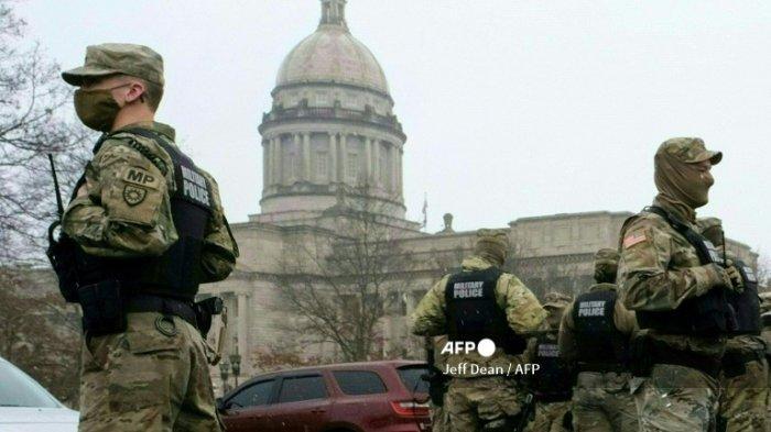 Anggota Garda Nasional berdiri di luar gedung DPR negara bagian di Frankfort, Kentucky, pada 17 Januari 2021, selama protes nasional yang diserukan oleh kelompok-kelompok anti-pemerintah dan sayap kanan pendukung Donald Trump