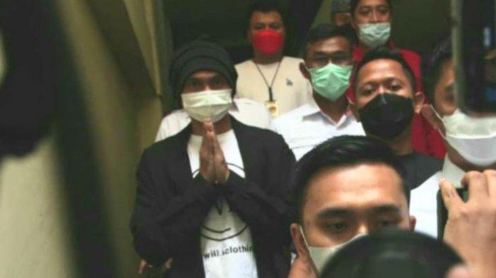 Anji eks Drive yang mengenakan kaos putih, kardigan hitam, masker, dan tutup kepala hitam terlihat terus menunduk ketika dibawa ke ruang pemeriksaan kesehatan.