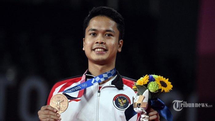 Anthony Sinisuka Ginting dari Indonesia berpose dengan medali perunggu bulu tangkis tunggal putra pada upacara selama Olimpiade Tokyo 2020 di Musashino Forest Sports Plaza di Tokyo. Senin (2/8/2021) (Alexander NEMENOV/AFP)
