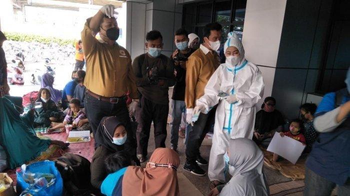 Pembagian uang tunai yang dilakukan Hasnaeni Moein yang akrab disapa wanita emas, dibubarkan petugas guna menghindari pelanggaran protokol kesehatan di posko pengungsian korban banjir Cipmel, Universitas Borobudur, Makasar, Jakarta Timur, Sabtu (20/2/2021)