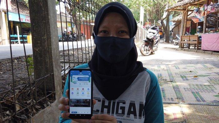 Sri Juliati menunjukkan aplikasi JKN Mobile yang terinstal di ponselnya, Senin (23/8/2021).