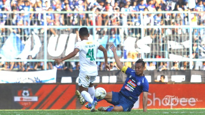 MENANG TELAK - Kapten Arema FC, Hamka Hamzah berebut bola dengan striker Persebaya Irfan Jaya dalam lanjutan Liga 1 di Stadion Kanjuruhan Kepanjen, Kabupaten Malang, Kamis (15/8/2019). Arema FC menang telak aras Persebaya Surabaya dengan skor 4-0. SURYA/HAYU YUDHA PRABOWO