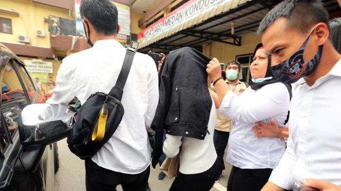 Polisi menggiring artis FTV yang berinisial HH di Mapolrestabes Medan, Sumatera Utara, Senin (13/7/2020). Artis FTV HH diamankan Satreskrim Polrestabes Medan atas kasus dugaan prostitusi yang digerebek di salah satu hotel berbintang di kota Medan pada Minggu (12/7) malam.TRIBUN MEDAN/RISKI CAHYADI