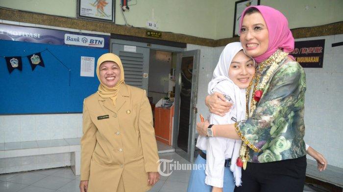 Anggota DPR RI komisi X, Arzeti Bilbina memeluk keponakannya Tania yang merupakan siswa kelas XII SMAN 2 saat melihat dari dekat proses ujian menggunakan komputer di SMAN 2 dan SMAN 1, Senin (6/3).
