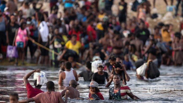 Imigran, sebagian besar dari Haiti berkumpul di tepi Rio Grande pada 19 September 2021 di Ciudad Acuna, Meksiko, di seberang perbatasan dari Del Rio, Texas. Ketika otoritas imigrasi AS mulai mendeportasi imigran kembali ke Haiti dari Del Rio, ribuan lainnya menunggu di sebuah kamp di bawah jembatan internasional di Del Rio dan yang lainnya menyeberangi sungai kembali ke Meksiko. John Moore/Getty Images/AFP