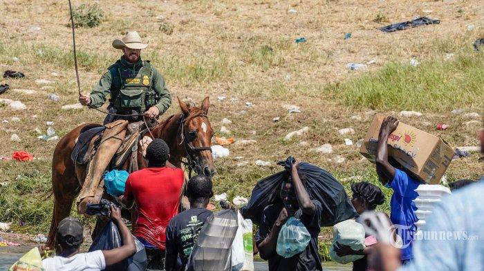 Seorang agen Patroli Perbatasan Amerika Serikat yang menunggang kuda menggunakan kendali saat ia mencoba untuk menghentikan migran Haiti memasuki perkemahan di tepi Rio Grande dekat Jembatan Internasional Acuna Del Rio di Del Rio, Texas pada 19 September 2021. Amerika Serikat Negara-negara bagian mengatakan Sabtu akan meningkatkan penerbangan deportasi bagi ribuan migran yang membanjiri kota perbatasan Texas Del Rio, ketika pihak berwenang berjuang untuk meringankan krisis yang berkembang bagi pemerintahan Presiden Joe Biden. AFP/PAUL RATJE