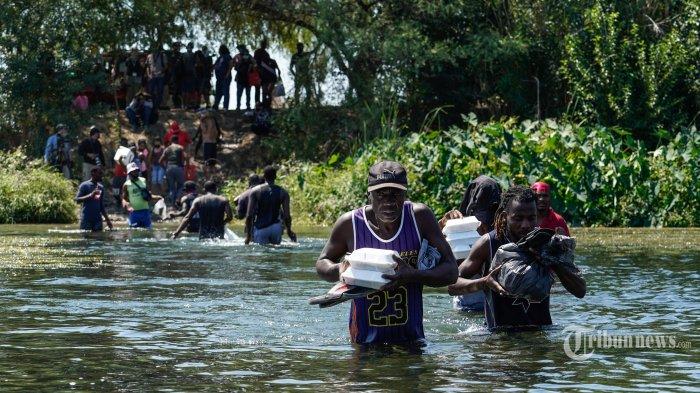 Migran Haiti, bagian dari kelompok lebih dari 10.000 orang yang tinggal di sebuah perkemahan di sisi perbatasan AS, menyeberangi sungai Rio Grande untuk mendapatkan makanan dan air di Meksiko, setelah titik penyeberangan lain ditutup di dekat Jembatan Internasional Acuna Del Rio di Ciudad Acuna, Meksiko pada 19 September 2021. Amerika Serikat mengatakan Sabtu akan meningkatkan penerbangan deportasi bagi ribuan migran yang membanjiri kota perbatasan Texas Del Rio, ketika pihak berwenang berjuang untuk meringankan krisis yang berkembang untuk pemerintahan Presiden Joe Biden. AFP/PAUL RATJE