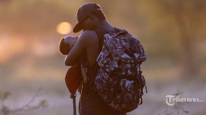 Seorang ayah berasal dari Haiti yang kelelahan menggendong putranya di sisi Meksiko Rio Grande dari Del Rio, Texas pada 19 September 2021 di Ciudad Acuna, Meksiko. Otoritas imigrasi AS mulai mendeportasi imigran kembali ke Haiti dari Del Rio, ribuan lainnya menunggu di sebuah kamp di bawah jembatan internasional di Del Rio dan yang lainnya menyeberangi sungai kembali ke Meksiko.  John Moore/Getty Images/AFP
