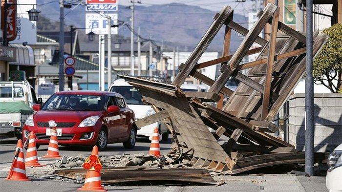 Atap rumah di Kori Fukushima ambruk ke jalan raya menghalangi kendaraan lalu lintas.