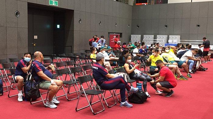 Atlet angkat besi dunia berkumpul duduk-duduk tanpa membersihkan lokasi latihannya menunggu petugas datang.