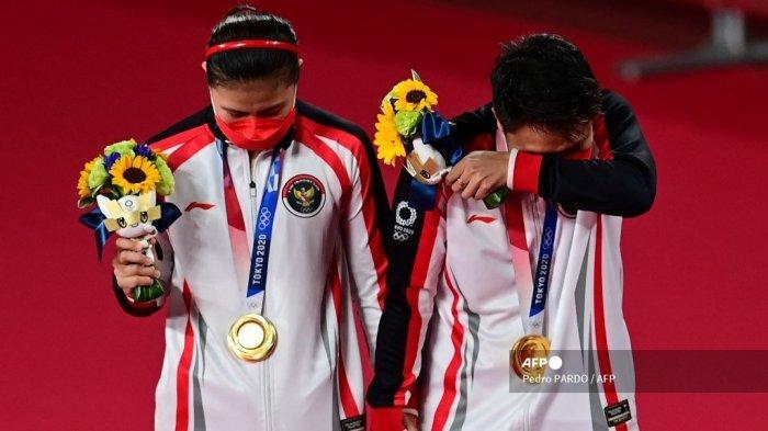 Atlet Indonesia Apriyani Rahayu (kanan) dan Greysia Polii Indonesia bereaksi dengan medali emas bulu tangkis ganda putri mereka pada upacara selama Olimpiade Tokyo 2020 di Musashino Forest Sports Plaza di Tokyo pada 2 Agustus 2021.