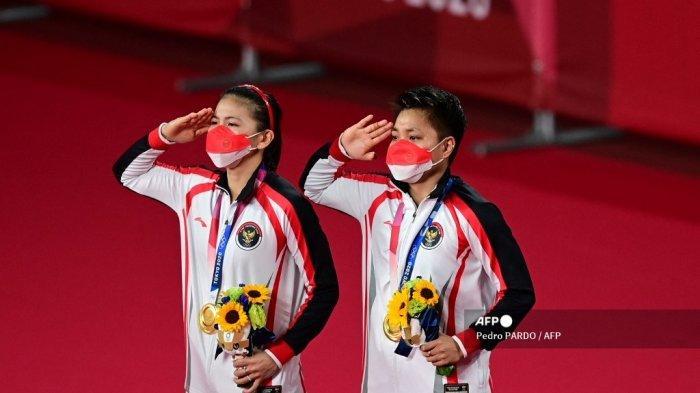 Atlet Indonesia Apriyani Rahayu (kanan) dan Greysia Polii Indonesia memberi hormat dengan medali emas bulu tangkis ganda putri mereka pada upacara selama Olimpiade Tokyo 2020 di Musashino Forest Sports Plaza di Tokyo pada 2 Agustus 2021.