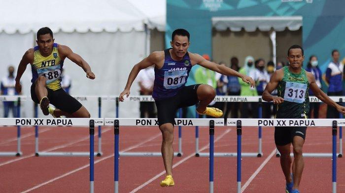 Atlet Jawa Barat, Halomoan EB (tengah ) berhasil meraih medali emas Atletik PON XX Papua nomor Lari 400m Gawang Putra setelah di babak final menjadi yang tercepat dengan catatan waktu 51,33 detik di Stadion Atletik Mimika Sport Center, Minggu (10/10/2021).