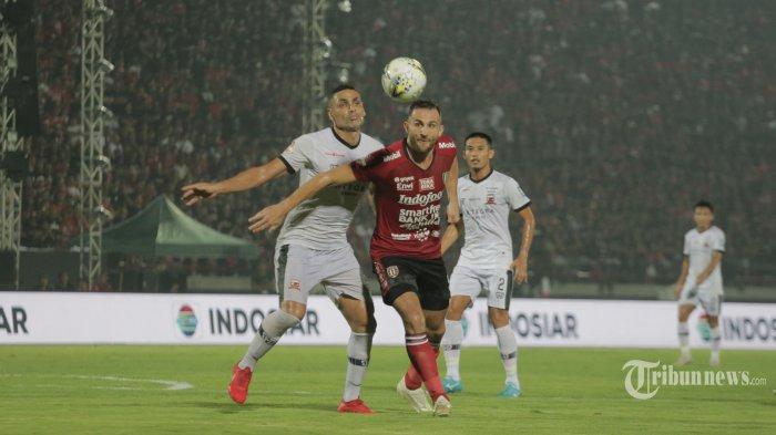 Pemain Bali United, Ilija Spasojevic (tengah) berebut bola dengan pemain Madura United, Jaimerson da Silva Xavier dalam laga penutup Liga 1 2019 di Stadion Kapten I Wayan Dipta, Gianyar, Bali, Minggu (22/12/2019) malam. Pada laga penutup tersebut Bali United kalah 0-2. Tribun Bali/Rizal Fanany