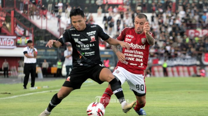 Pemain Bali United, Paulo Sergio berebut bola dengan pemain Madura United, Abimanyu dalam pertandingan Liga 1 pekan ke 3 di Stadion Dipta, Gianyar, Bali, Minggu (15/3/2020). Bali United menang 3-1.(Tribun Bali/Rizal Fanany)