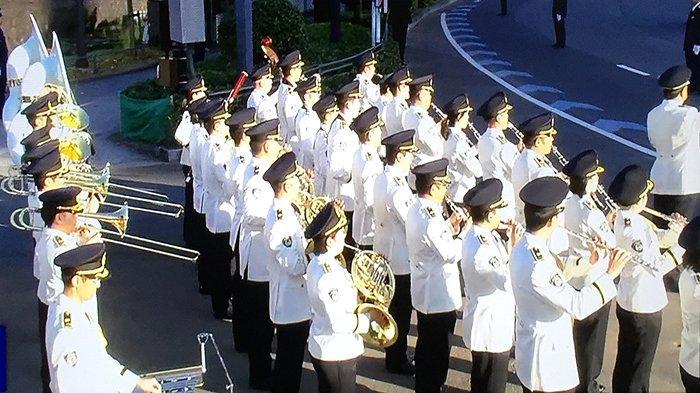 Band musik kepolisian Jepang melantunkan lagu saat mobil Kaisar dan permaisuri melewatinya.