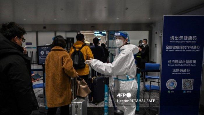 Penumpang yang mengenakan masker pelindung sebagai tindakan pencegahan terhadap Covid-19 (virus corona baru) berjalan di sektor tempat kode kesehatan mereka diperiksa, di Bandara Internasional Tianhe di Wuhan, di provinsi Hubei tengah China pada 27 Januari 2021.