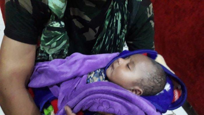 Bayi berusia 5 bulan yang berhasil diselamatkan anggota TNI dari Yonif RK 751/VJS saat terjadi banjir bandang di Kota Sentani, Minggu (16/3/2019). Bayi tersebut sebelumnya enam jam terjebak di kolong rumah.