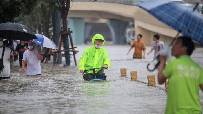 Foto ini diambil pada 20 Juli 2021 menunjukkan seorang pria mengendarai sepeda melalui air banjir di sepanjang jalan setelah hujan lebat di Zhengzhou di provinsi Henan, China tengah.