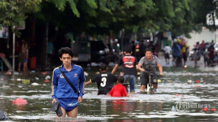 Sejumlah warga nekat melewati banjir yang merendam Jalan Kartini, Bekasi, Jawa Barat, Kamis (2/1/2020). Arus lalu lintas di jalan tersebut lumpuh total, pemukiman warga, toko, hingga rumah sakit terendam banjir setinggi pinggang orang dewasa serta kendaraan yang tidak sempat dievakuasi juga nampak terendam banjir hingga menutup seluruh badan mobil. Tribunnews/Jeprima