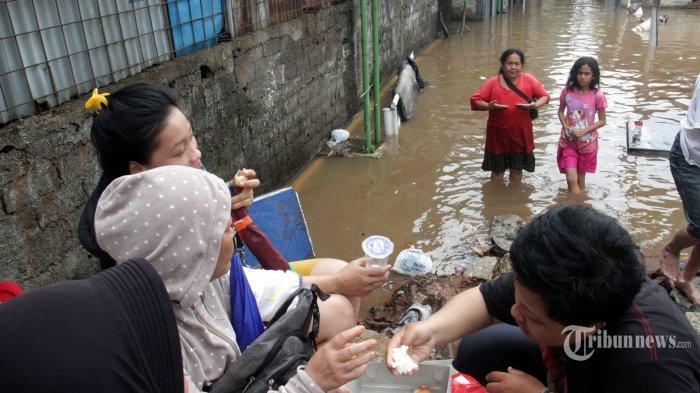 Warga beraktivitas di tengah genangan banjir di kawasan Kampung Pulo, Kampung Makasar, Jakarta Timur, Rabu (1/1/2020). Banjir yang melanda kawasan tersebut kedalamannya mencapai 1,5 meter. Tingginya curah hujan membuat sejumlah wilayah di Jakarta dan sekitarnya mengalami kebanjiran.